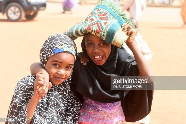 Young girls carry a prayer mat as they walk close to the Central Mosque in Daura Katsina State the home of the ruling All Progressives Congress...