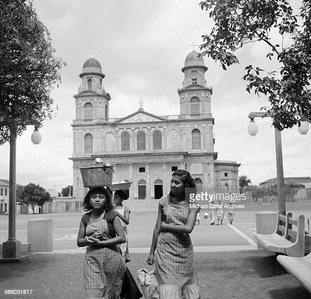 Young girls carry buckets on their heads as they walk in front of the Old Cathedral of Managua in Managua Nicaragua