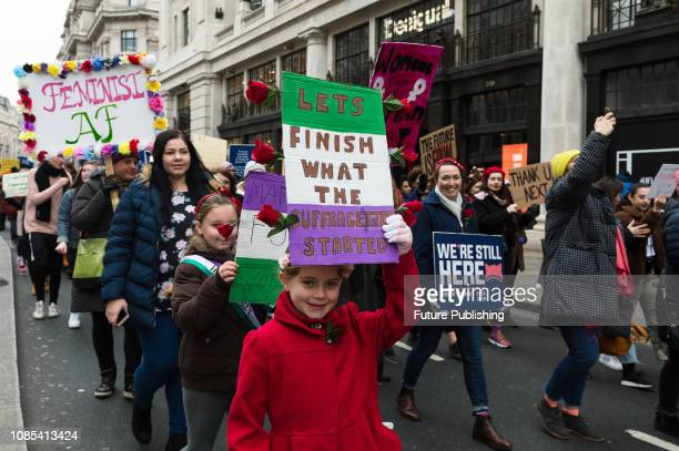 Young girls carry suffragette placards as thousands of women participate in 'Women's March for Bread and Roses' in central London as part of global...