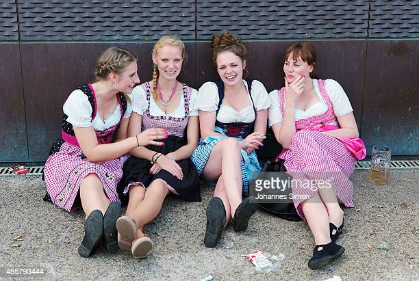 Young girls chat together sitting on the floor outside a beer tent during the opening day of the 2014 Oktoberfest on September 20 2014 in Munich...