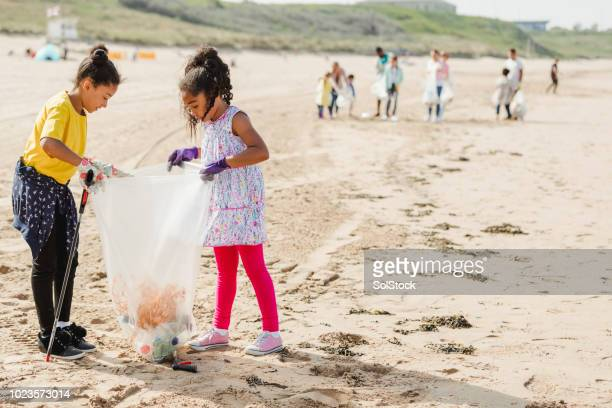 young girls collecting plastics and rubbish off a beach - campaigner stock pictures, royalty-free photos & images