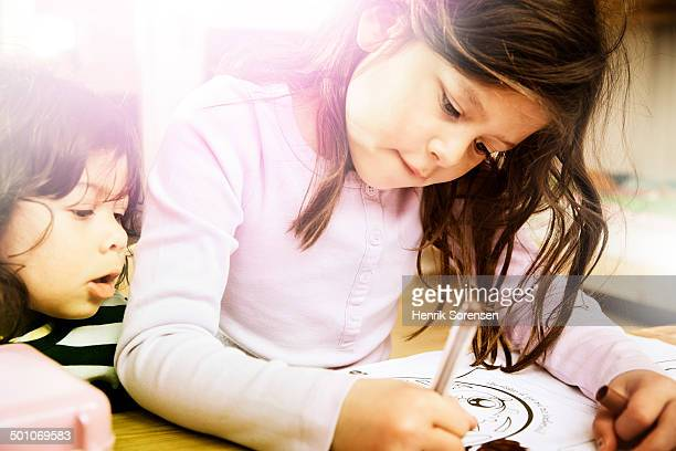2 young girls coloring a book