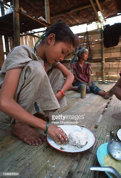 Young girls eat rice sitting on the floor of their wood and bamboo hut in a new Karen refugee camp north of the Thai town, Mae Sot. They are recent...
