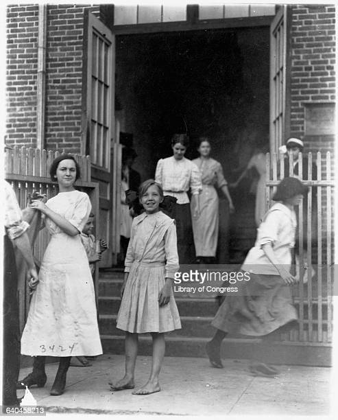 Young girls employed at a mill hurry out of the building and head home after a workday | Location Massey Hosiery Mills Columbus Georgia USA