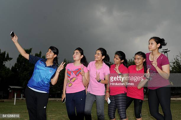 Young girls enjoy cloudy weather at Punjabi University on June 18 2016 in Patiala India Premonsoon rains lashed many parts of Punjab and Haryana...