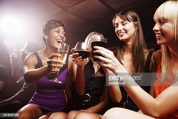 Jeunes filles appréciant des boissons et un toast à une soirée