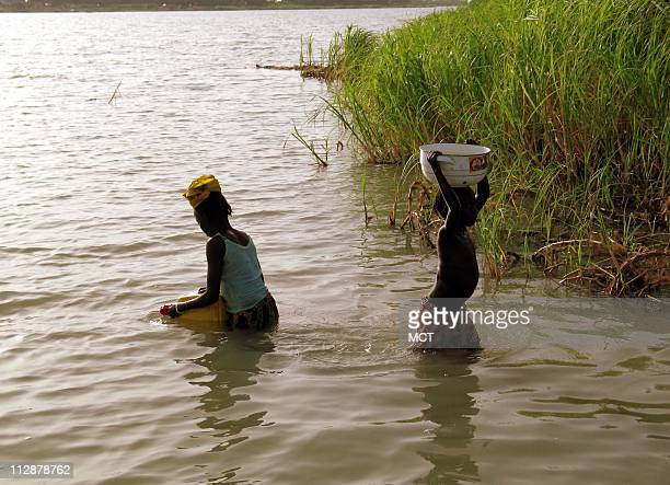 Young girls fetch lake water for their village on the banks of Lake Chad One of the largest lakes in the world central Africa's Lake Chad is drying...
