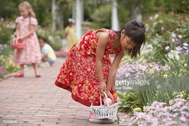 Young girls gathering Easter eggs in garden