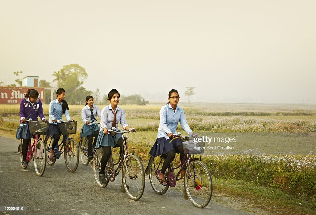 young girls going to school on their bicycle : Stock Photo