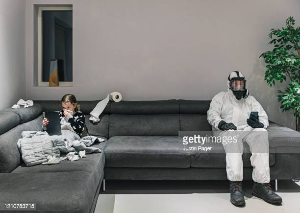 young girls got the flu. dad's in his full protective gear on other end of the sofa! - pandemic illness stock pictures, royalty-free photos & images
