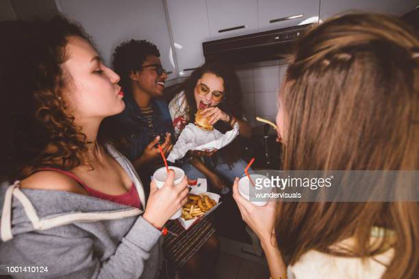 young girls having fun eating fast food at house party - take away food stock pictures, royalty-free photos & images