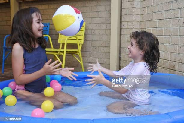 young girls having fun in inflatable pool - rafael ben ari stockfoto's en -beelden