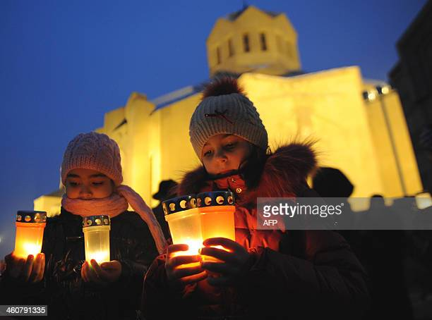 Young girls hold candles outside Saint Gregory the Illuminator church in the Armenian capital of Yerevan during an Armenian Orthodox Christmas Eve...