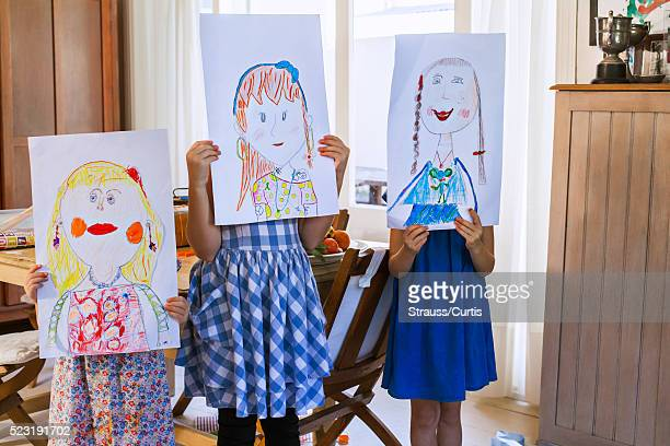 Young girls (6-7, 10-12) holding paintings in front of faces