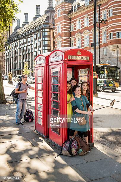 Young girls in a phone box, London