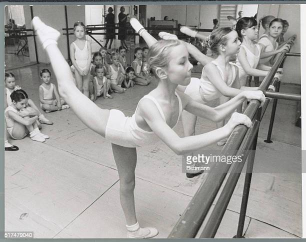 Young girls in ballet class perform an arabesque pose at the bar as their classmates