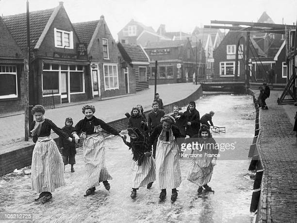 Young Girls In Traditional Dress Make Ice Skates On A Frozen Canal While Boys Are Tobogganing In The Region Of Volendam In Holland February 10 1959