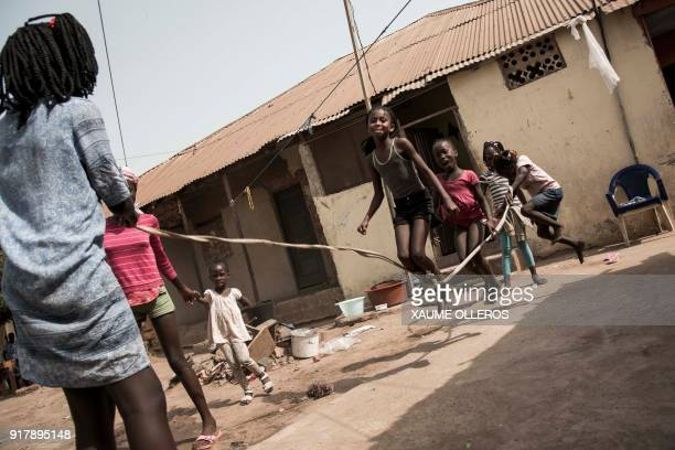 TOPSHOT Young girls jump rope in the Mindara neighbourhood in Bissau on Mardi Gras on February 13 2018 / AFP PHOTO / Xaume Olleros