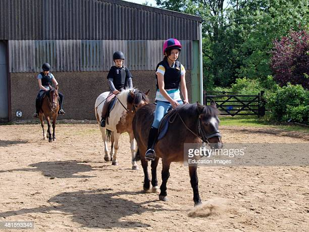 Young girls learning to horse ride at stables UK