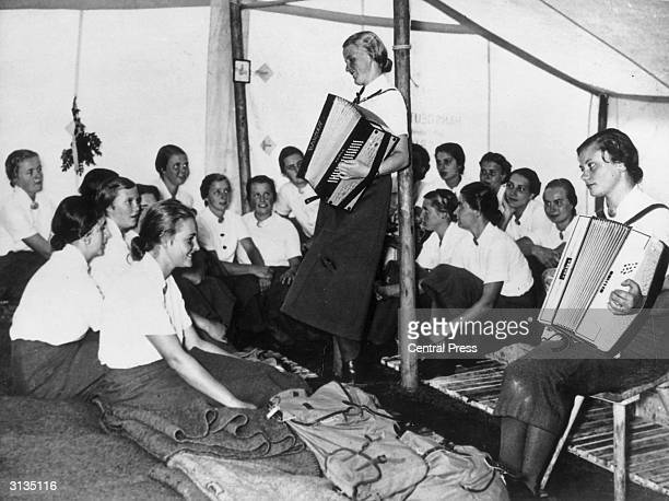 Young girls listening to two accordion players at a Hitler Youth summer camp in Germany.