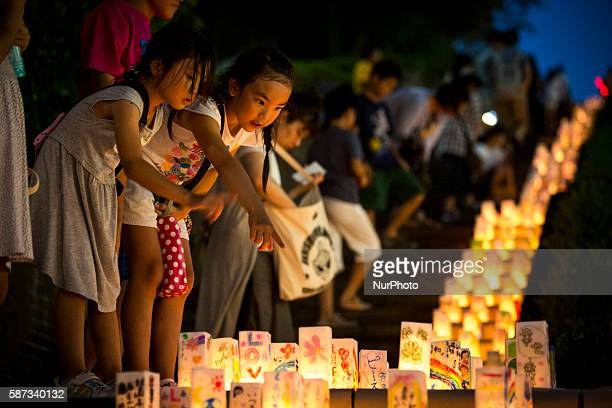 Young girls look at candlelit paper lanterns with written message at Nagasaki Peace Park on the eve ahead of the 71st anniversary activities...