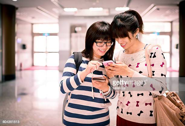 young girls looking at smart phone - leren stock pictures, royalty-free photos & images