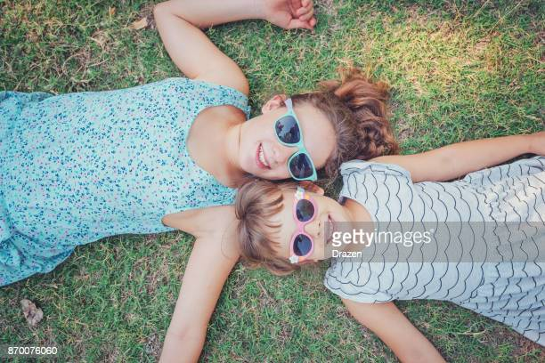 Young girls lying on the grass in park and smiling