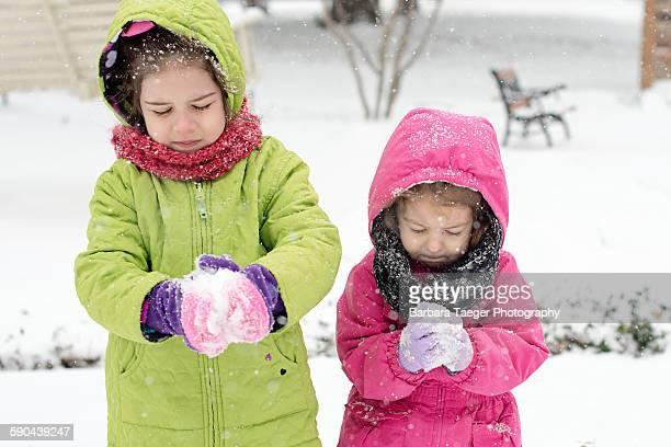 Young girls making snowballs