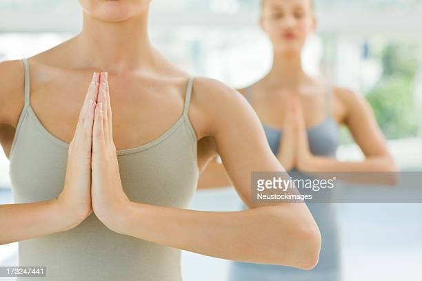 Young girls meditating with hands joined