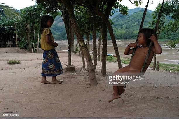 Young girls one on a swing in Hoykhe Village with 42 houses and 32 Hmong inhabitants on the Mekong River 50 km north of Luang Prabang is a popular...