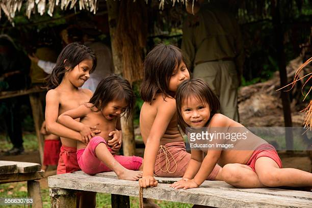Young girls pay on a bench in a village on the Amazon River Peru