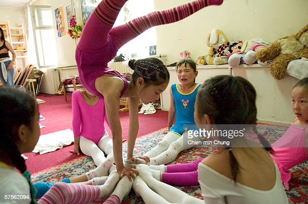 Young girls perform stretching exercises at the contortionist school in the Mongolian Circus June 30 2005 in Ulaanbaatar Mongolia Bolor Batjargal...