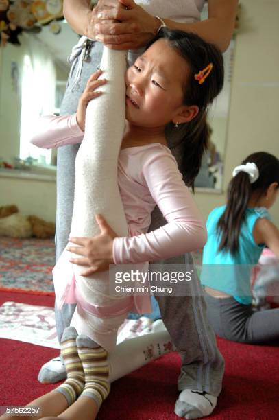 Young girls perform stretching exercises at the contortionist school in the Mongolian Circus July 19 2005 in Ulaanbaatar Mongolia The school trains...