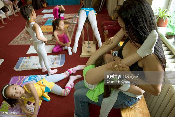 Young girls perform stretching exercises at the contortionist school in the Mongolian Circus June 30 2005 in Ulaanbaatar Mongolia The school trains...