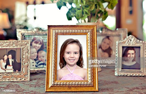 young girl's picture in a frame with others behind - fotografie stock-fotos und bilder
