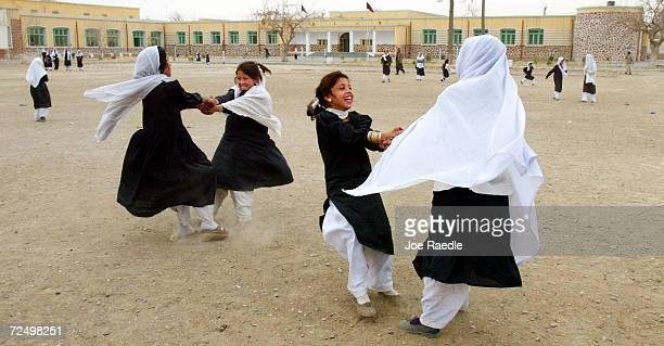 Young girls play a game of spinning each other around in a circle on the playground of the Zhargona Ana high school February 25 2002 in Kandahar...