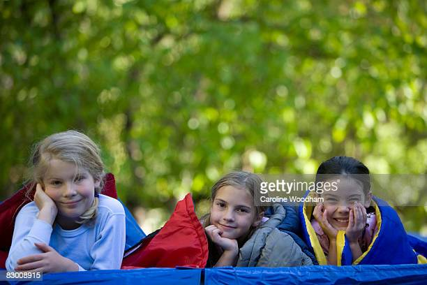 young girls play on trampoline in sleeping bags. - ketchum idaho stock photos and pictures