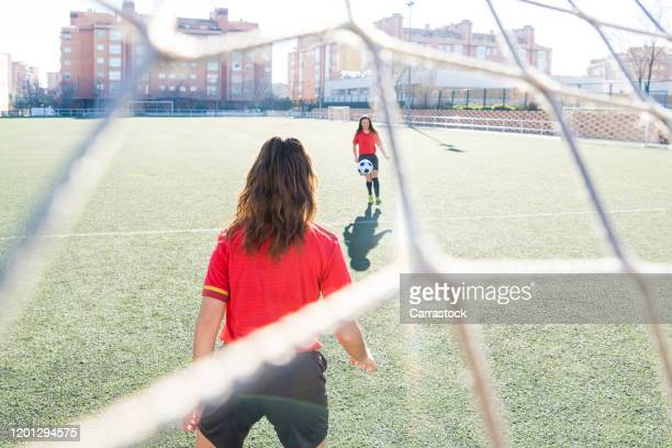 Young girls playing football in grass field.