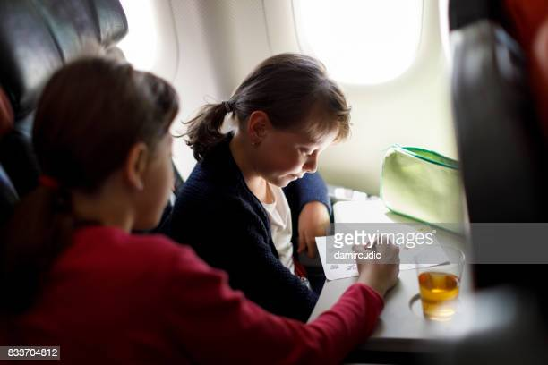 Young girls playing game on the airplane