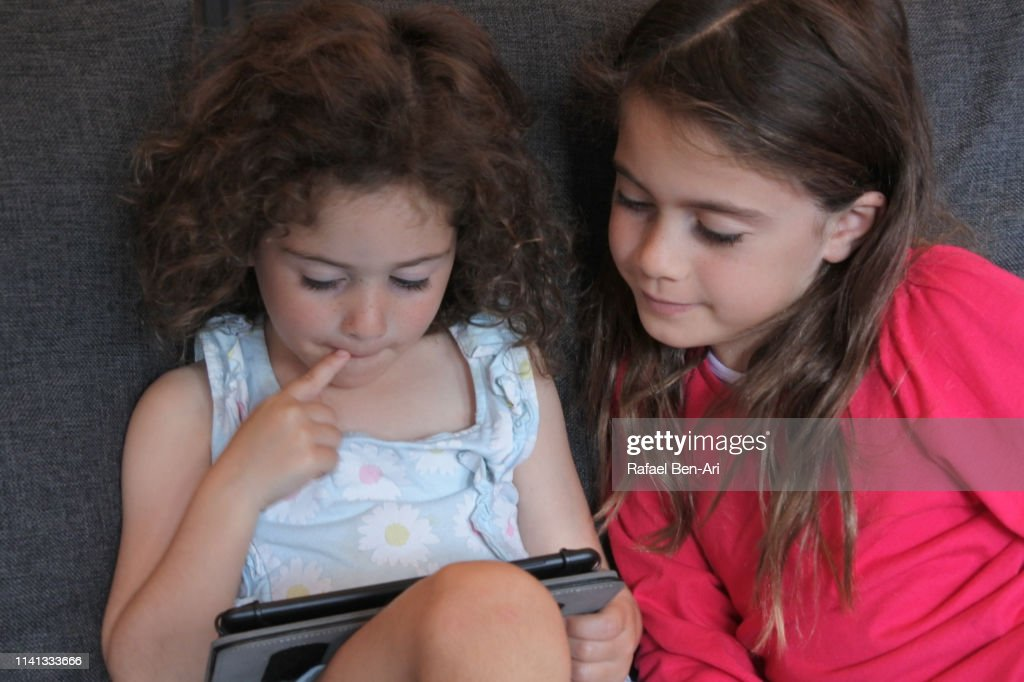 Young girls playing on a tablet : Stock Photo