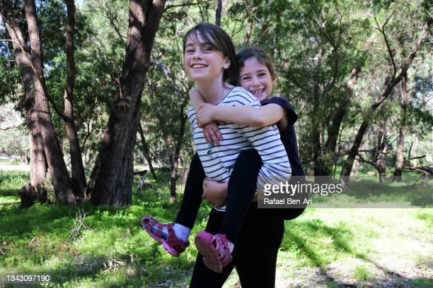 young girls playing piggyback ride at the park - rafael ben ari - fotografias e filmes do acervo