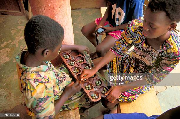 Young girls playing the African board game owari in Kumasi, the capitol of the Ashanti Region of Ghana, West Africa.