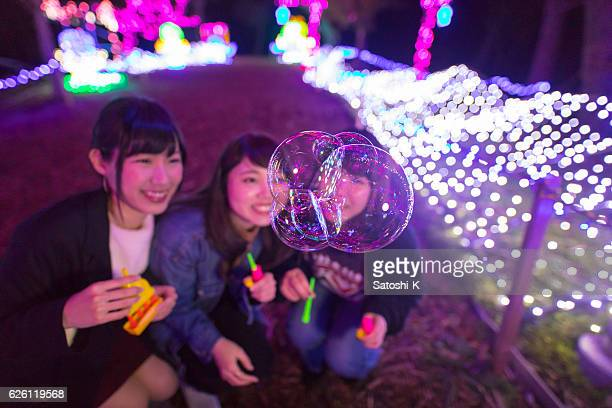 young girls playing with bubbles in christmas lights - chiba city stock pictures, royalty-free photos & images