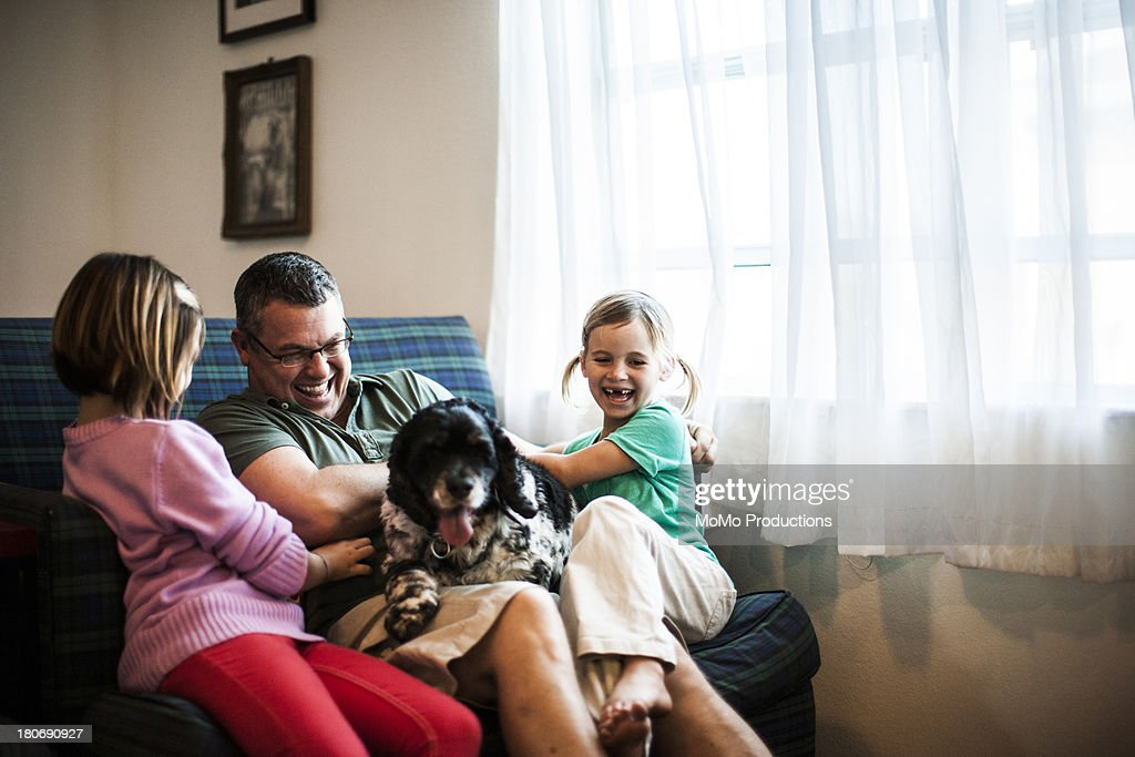 young girls playing with father and dog : Stock Photo