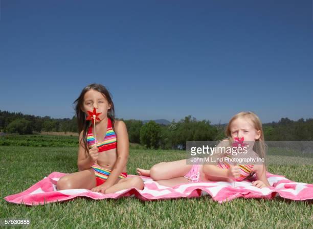 young girls playing with pinwheels - solo bambine femmine costume da bagno foto e immagini stock