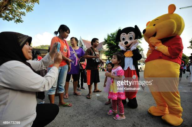 Young girls pose for a photograph with Walt Disney mascots during Thailand's National Children's Day in Ranong city Thailand's National Children's...