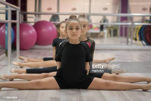 jeunes filles se préparant pour la formation de ballet à l'intérieur - gymnastique au sol photos et images de collection