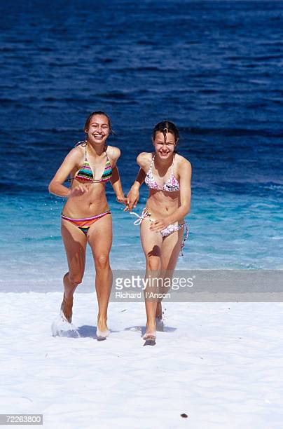 Young girls running on Whitehaven Beach in the Whitsunday Islands, Whitsunday Islands National Park, Australia