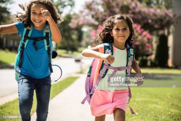 young girls running outside wearing backpacks - education stock pictures, royalty-free photos & images