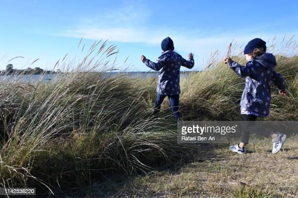 young girls running to the beach - rafael ben ari stock-fotos und bilder